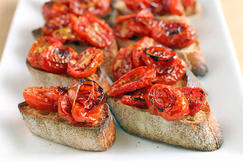 Roasted tomatoes top baguette toast, on a rectangular white serving platter, on a beige background.