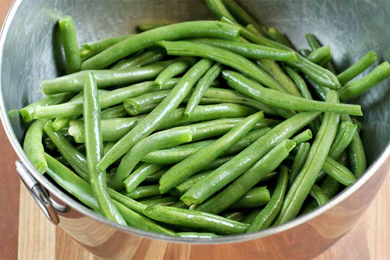 Fresh green beans with the ends removed, in a stainless steel bowl, on a striped wooden background.