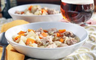 Two shallow soup bowls filled with Oktoberfest stew with potatoes, carrots, and German sausage, with a glass of lager, on a beige and white tablecloth with a yellow cloth napkin and a spoon.