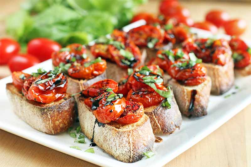Roasted tomato crostini topped with chopped basil and a balsamic drizzle, on a white rectangular ceramic serving dish, with fresh produce and herbs in the background, on a beige wood surface.