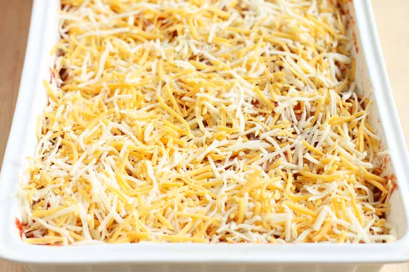 Shredded white and yellow cheese is scattered on the top of a red sauce in a white ceramic casserole dish, on a beige background.