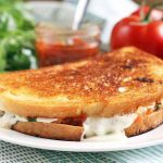 Side view of a grilled cheese sandwich on a plate, with basil, a small jar of red jam, and tomatoes in the background, on a blue and white checkered cloth.
