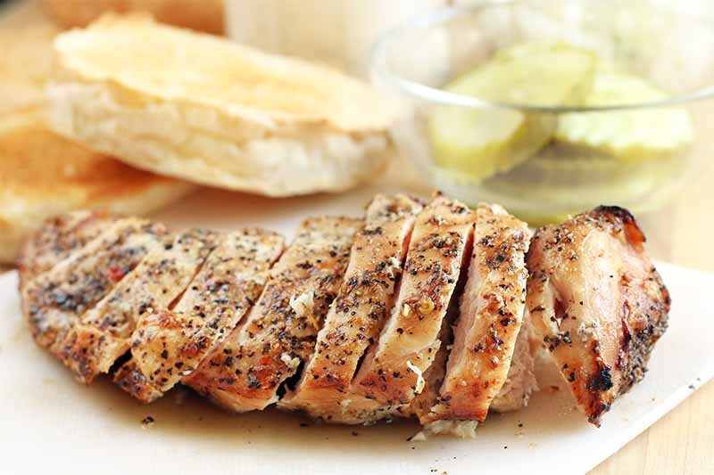 Sliced grilled chicken breast rubbed with spices is in the foreground on a white plastic cutting board, with a sliced and toasted kaiser roll and a small dish of pickles, on a beige countertop.