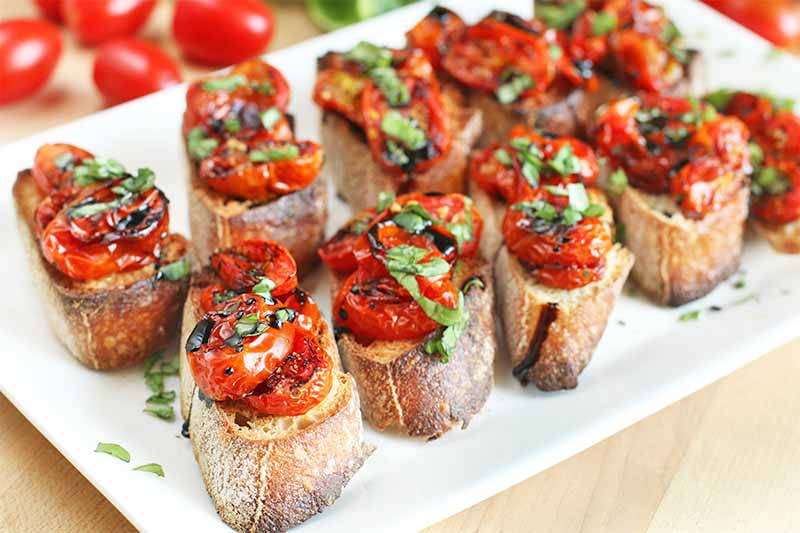 Roasted grape tomato crostini with fresh basil and a balsamic reduction are arranged on a white serving platter, with fresh produce in the background at the top left corner of the frame.
