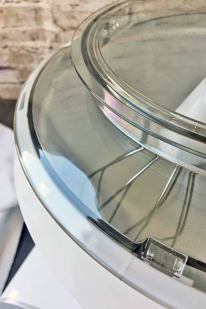 Vertical image of a double plastic lid and a whisk.