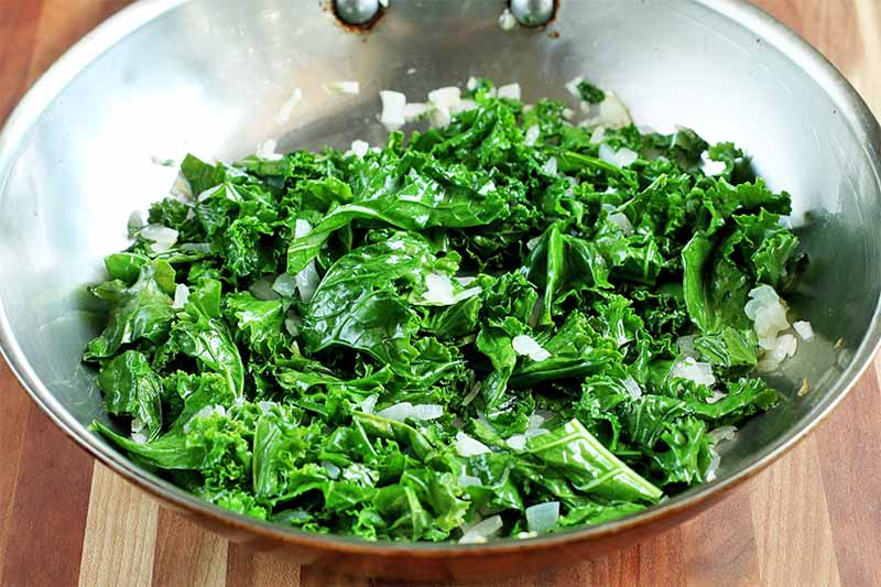 A large silver-colored frying pan of sauteed green kale and onions, on a brown wood surface.