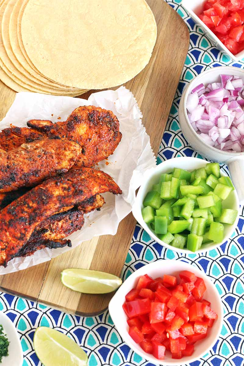 Top-down spot of blackened Cajun chicken tenders on a crumpled piece of parchment, small white bowls of chopped red and green bell pepper, purple onion, and tomato, lime wedges, and a stack of tortillas on a wood cutting board, on a dark and light blue patterned cloth surface.
