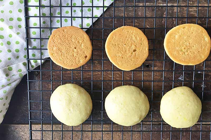 Horizontal image of six cake rounds, three with the bottoms facing up, on a cooling rack.
