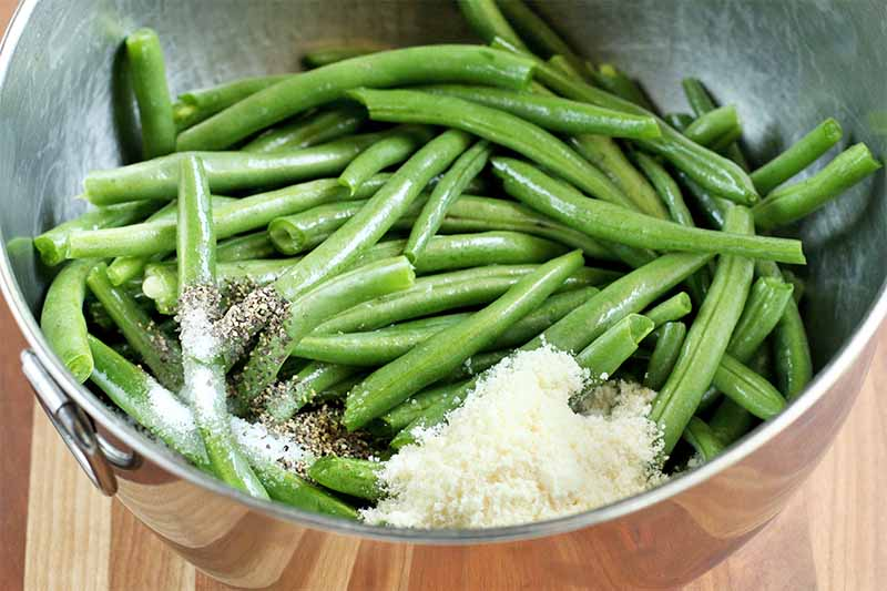 A stainless steel mixing bowl of green beans, salt, pepper, and grated parmesan, on a brown wood surface.