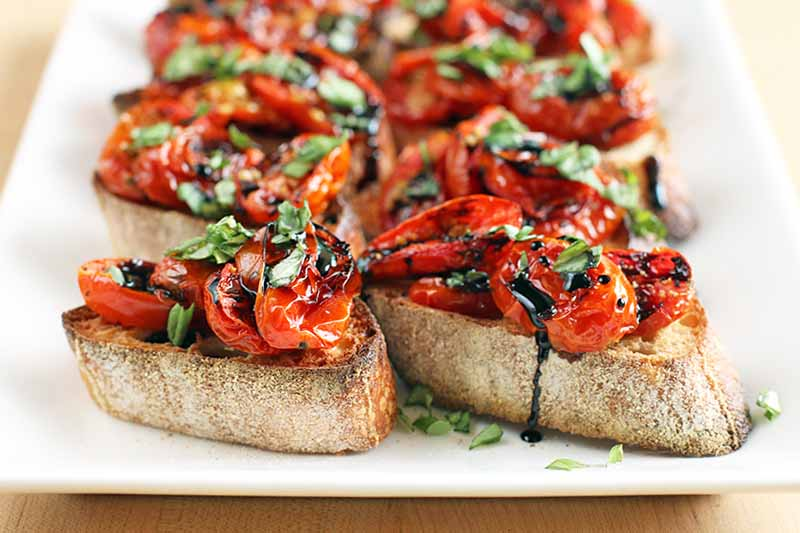 Baguette toasts topped with roasted tomatoes, fresh basil, and a balsamic reduction sauce, on a beige background.