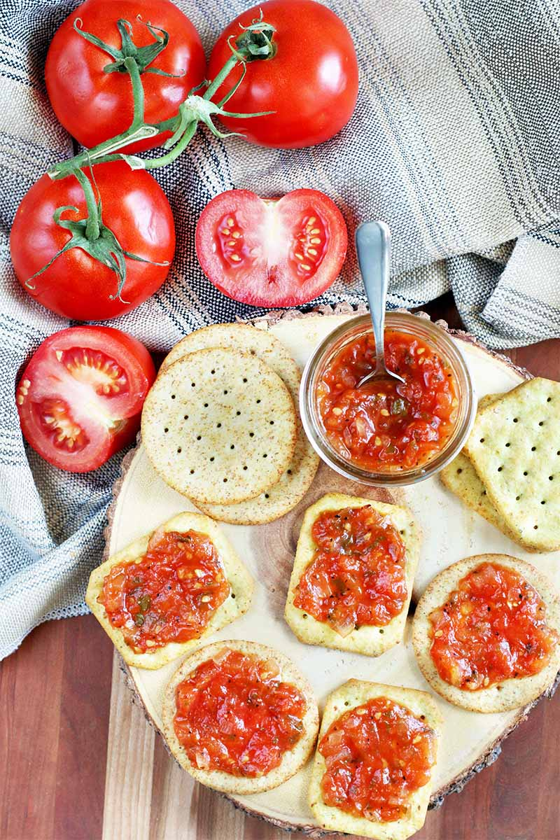 Top-down shot of crackers and tomato jam on a wood display board, with halved and whole tomatoes on the vine on a gray cloth.