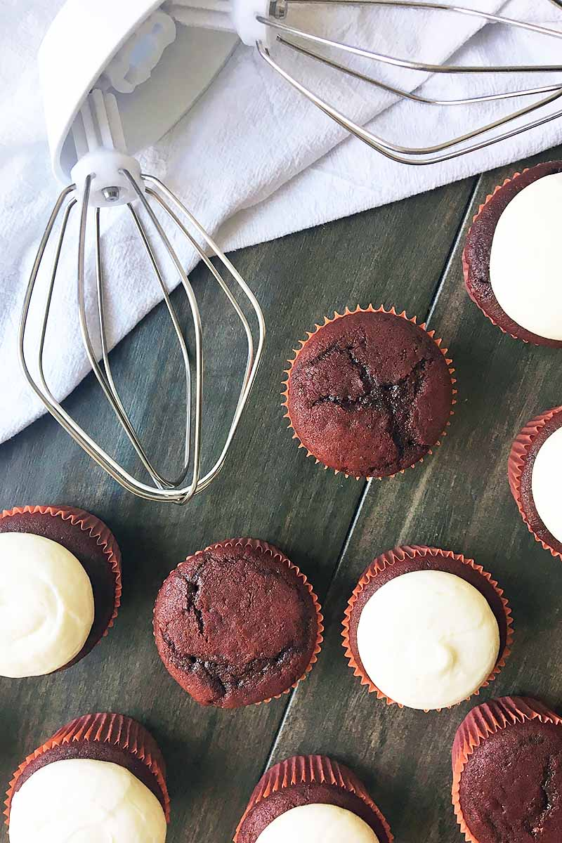 Vertical image of a wire whip on a white towel with cupcakes on a wooden surface.