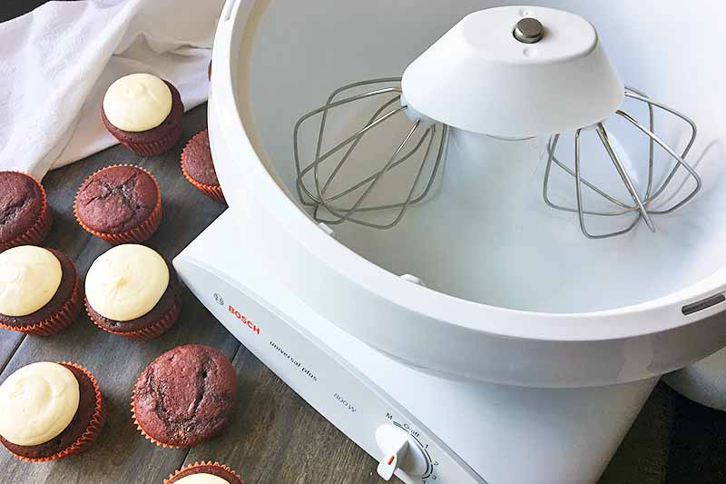 Horizontal image of the Universal Plus machine, with decorated and undecorated red cupcakes.