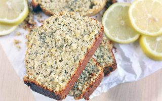 Sliced lemon poppy seed bread piled on a crumpled piece of white parchment paper, with lemon slices, on a beige surface.