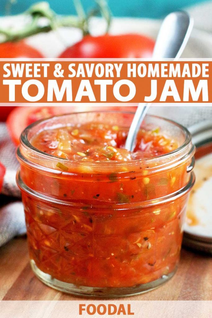 A jar of homemade tomato jam with a spoon stuck into it, with tomatoes on the vine in shallow focus, nestled in a gray cloth against a blue background, on a wood surface, with orange and white text.