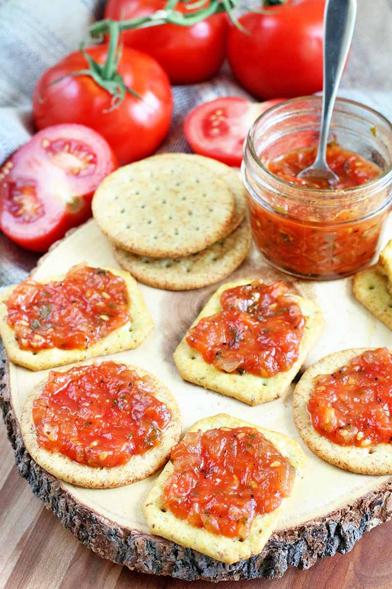Tomato jam spread on crackers arranged on a decorative slice of a wood log with bark, with a small jar of the mixture and a spoon, alongside halved and whole tomatoes on the vine, on a light brown wood surface.