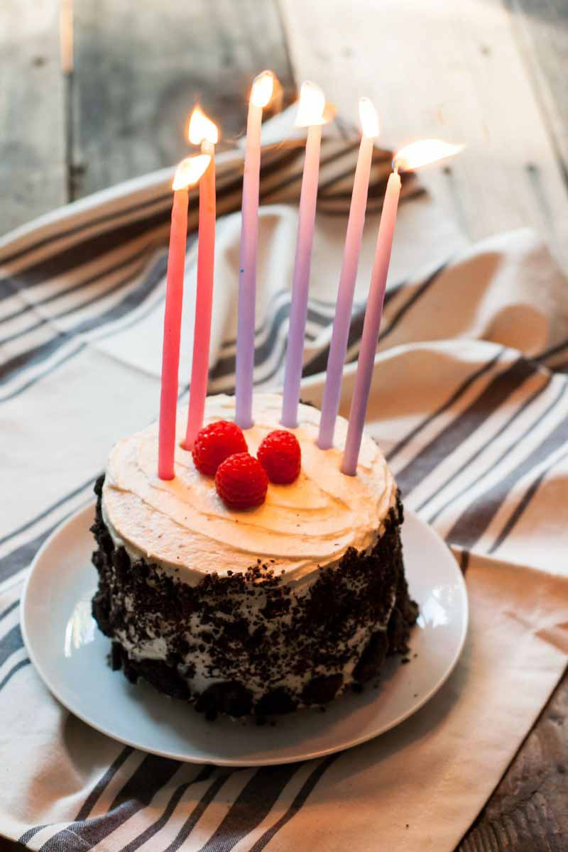 Vertical image of lit candles on top of a decorated cake on a white plate.