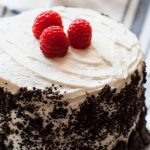 Horizontal close-up image of a decorated dessert with white icing, three raspberries, and cookie crumbles covering the sides.