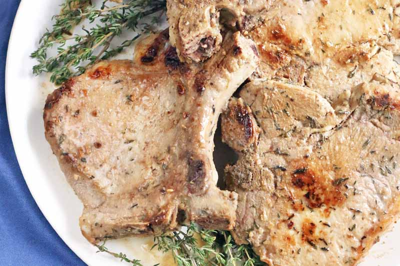 Bone-in pork chops piled on a white plate with thyme sprigs for garnish, on a blue cloth background.