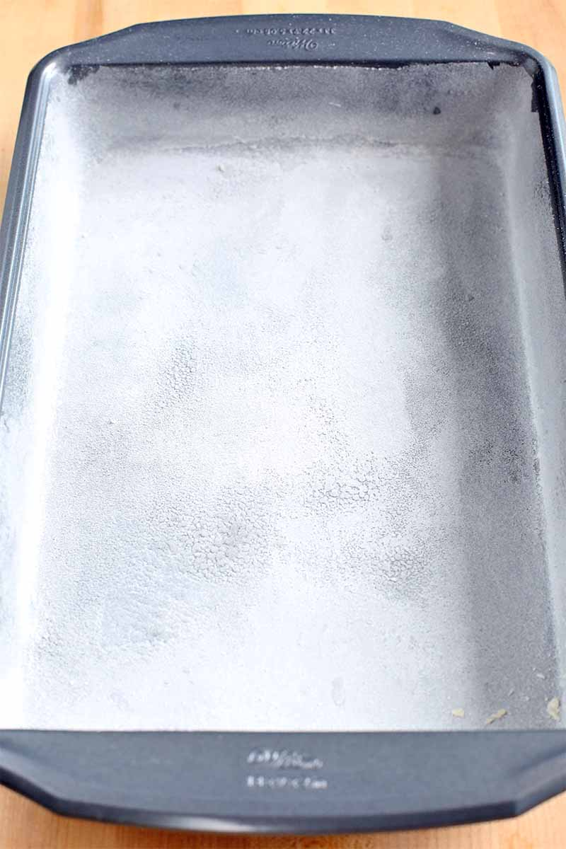 "Top-down image of a large 9x13"" metal baking pan, coated with oil and flour, on a beige surface."