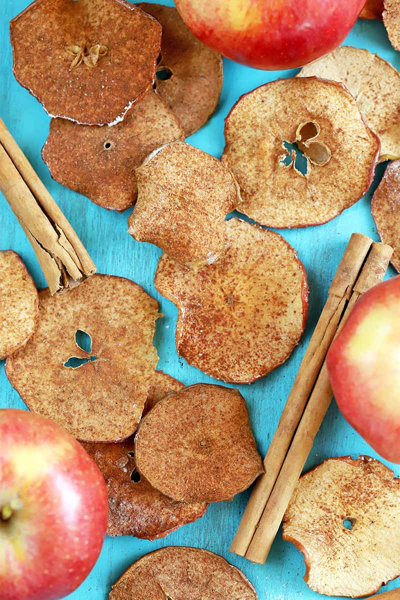 Top-down vertical image of homemade spiced apple chips, cinnamon sticks, and three whole fruit, on a light blue background.
