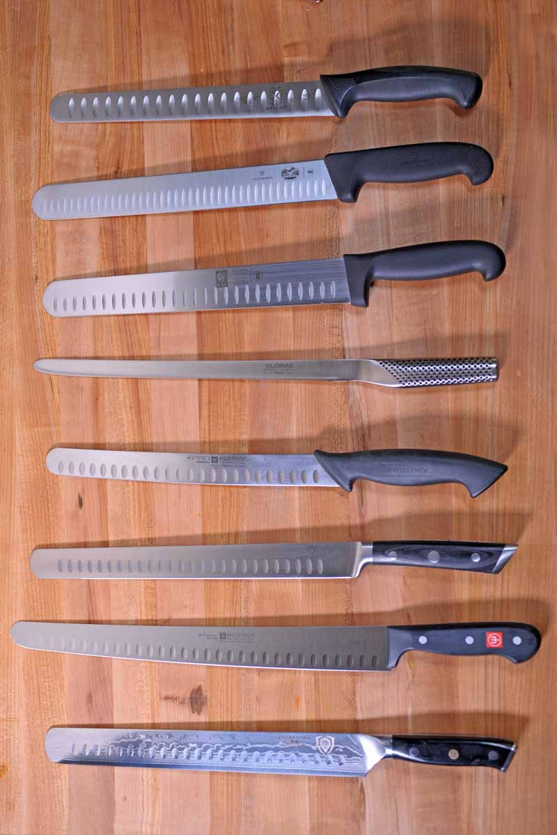 Top down view of eight slicing knives on a maple table top.