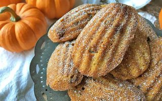 Horizontal image of stacked shell cookies dusted with powdered sugar with pumpkins in the background.