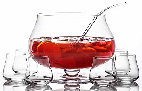 Crystal footed punch bowl filled halfway with a red liquid and sliced fruit, with ladle and six glasses, isolated on a white background.