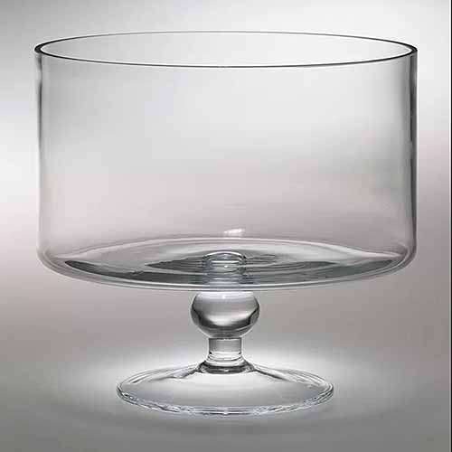 A crystal trifle serving dish with pedestal, isolated on a gray background with variable lighting and shadows.