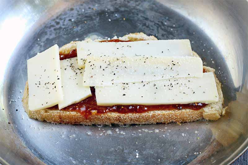 Sliced gruyere cheese on top of a piece of sourdough bread slathered with fig jam, in a frying pan.