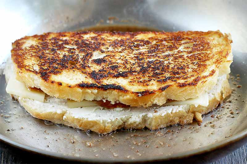 A grilled cheese sandwich being cooked in a frying pan.