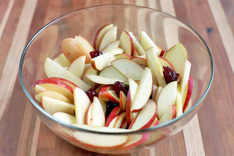 A large glass bowl of sliced red apple and cranberries, on a striped dark and light brown wood surface.