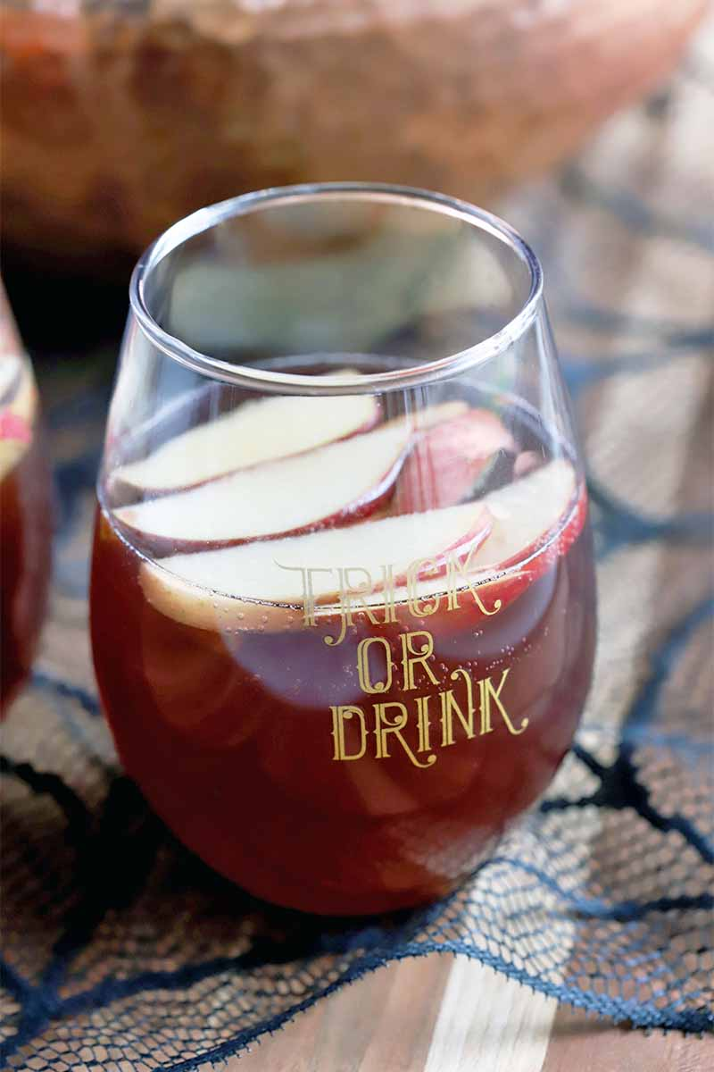"A glass that reads ""Trick or Drink"" in gold lettering is filled halfway with a red liquid with sliced apples floating on top, on a black lace spiderweb placemat with a copper punch bowl in the background."