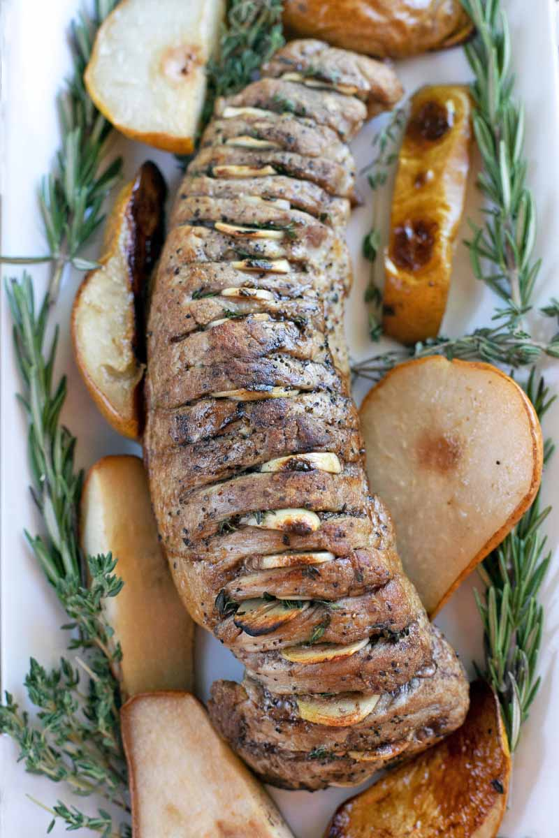 Overhead vertical shot of a roasted pork tenderloin with garlic and herbs inserted in slits running down the length of the meat, with roasted pears and fresh sprigs of rosemary and thyme, on a white serving platter.
