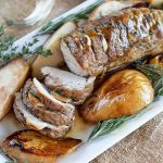 Partially sliced roasted pork tenderloin with pears, rosemary, and thyme, on a rectangular white ceramic serving platter, on a burlap surface.