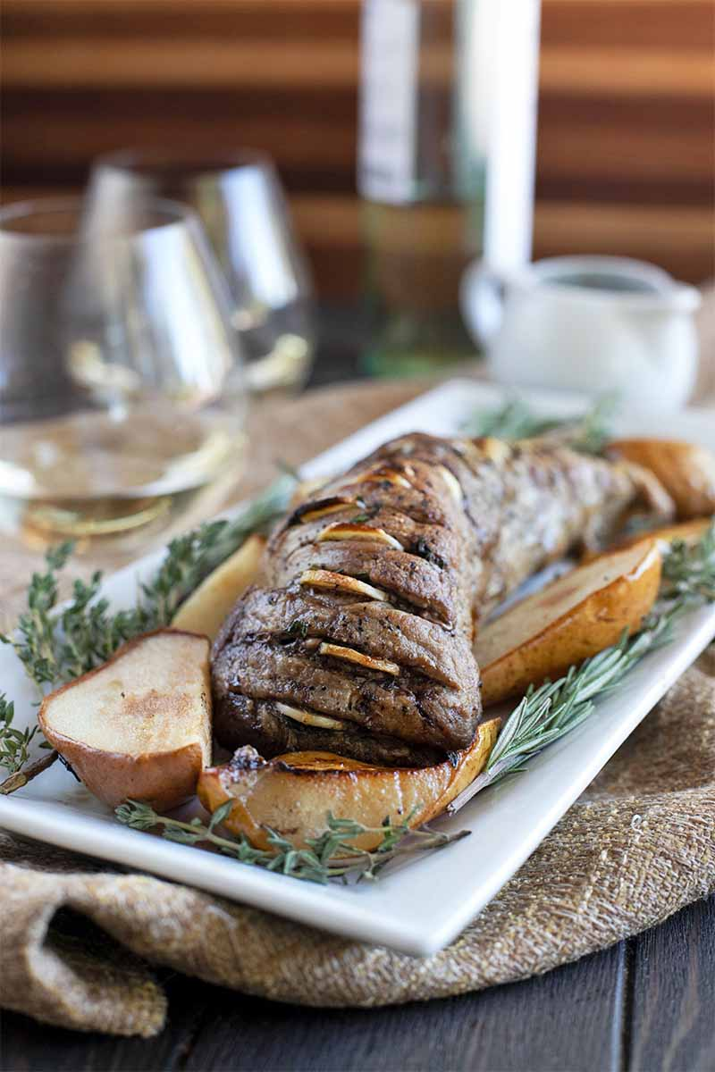 Roasted pork tenderloin with pears and fresh rosemary and thyme, on a rectangular whit serving platter on top of a piece of burlap with wine glasses and a white gravy pitcher in soft focus.