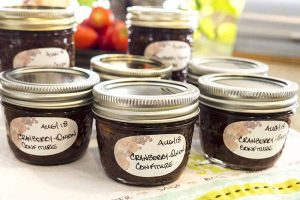"Jars filled with a maroon confit, with handwritten labels that say ""Aug 18"" and ""Cranberry-Onion Confiture,"" on a patterned kitchen towel."