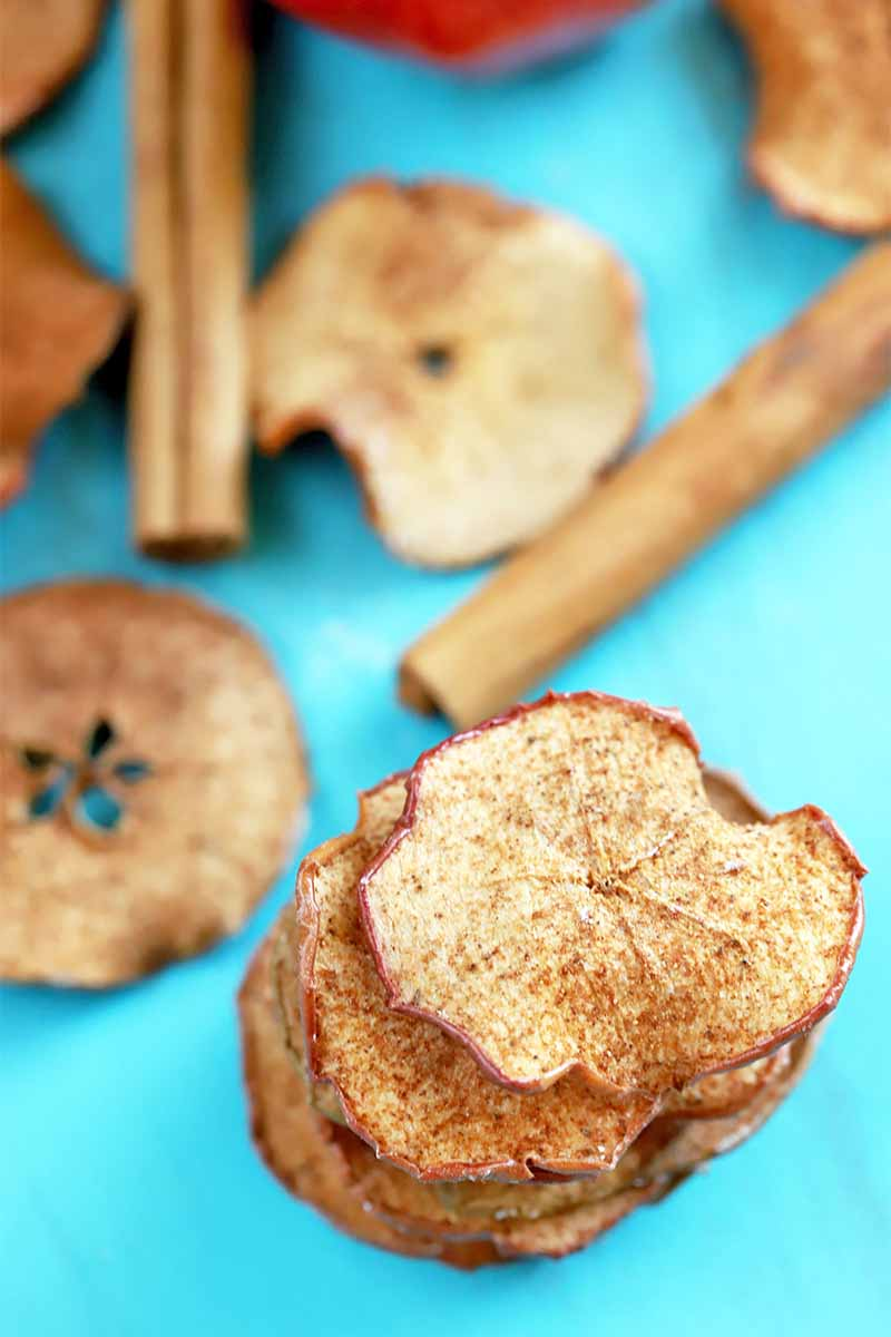 A small stack of homemade baked apple chips is in the foreground, with more scattered alongside two whole cinnamon sticks in the background, on a bright blue surface.