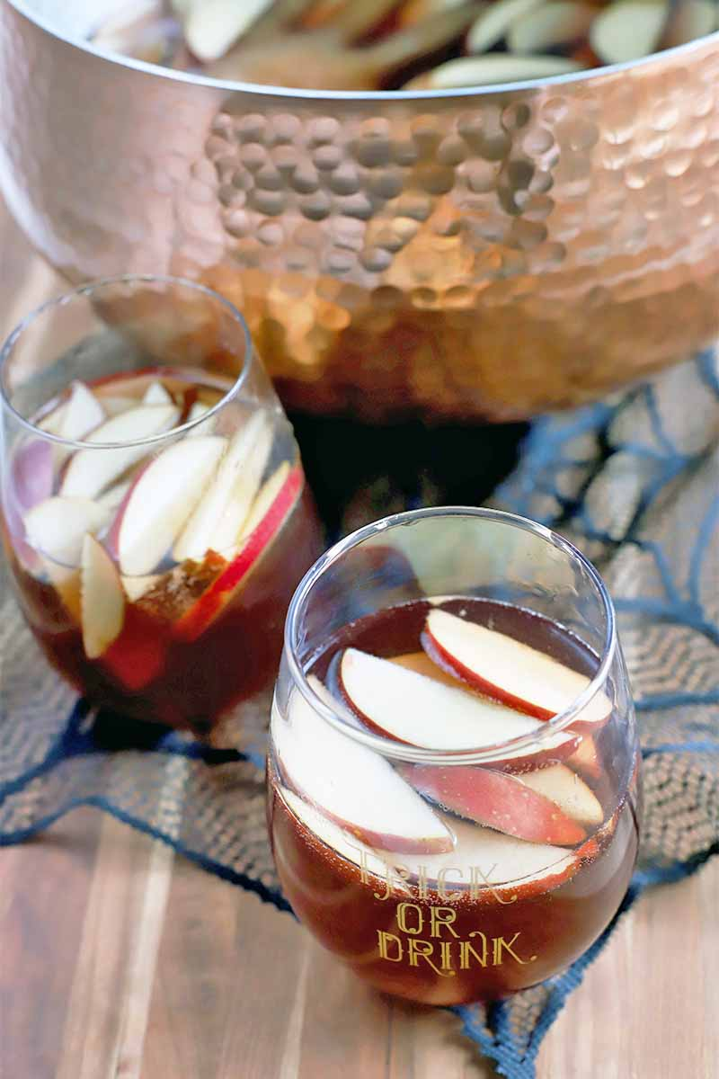 Oblique shot of two glasses filled with red punch and sliced fruit, in front of a copper punch bowl, on a spiderweb-shaped black lace cloth, on a striped wood tabletop.