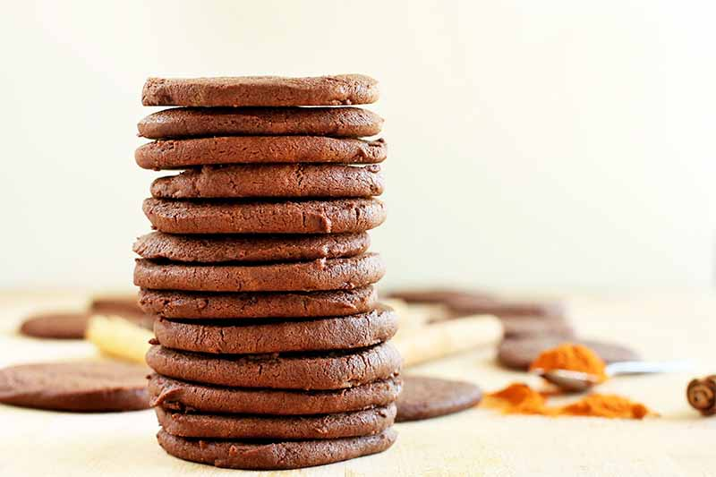 A stack of 13 chocolate cookies in the foreground, with more of the baked treats, cinnamon sticks, and a spilled spoonful of cayenne pepper in soft focus in the background, on a beige surface against an off-white wall.