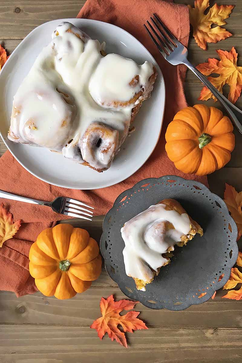 Vertical image of a half-eaten iced bun and a plate of whole pastries with orange squashes.