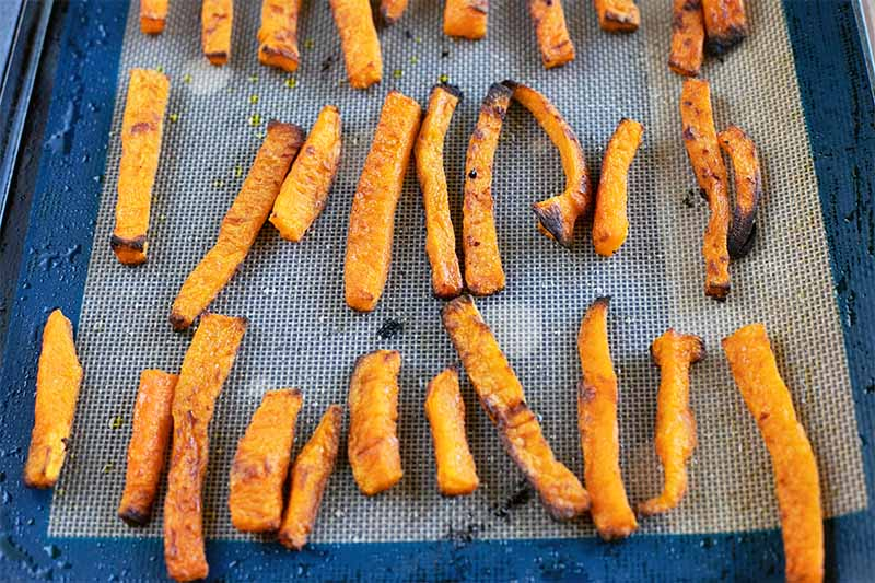 Homemade squash fries arranged on a blue and gray silicone mat on a baking sheet, topped with a single layer of baked butternut squash fries.