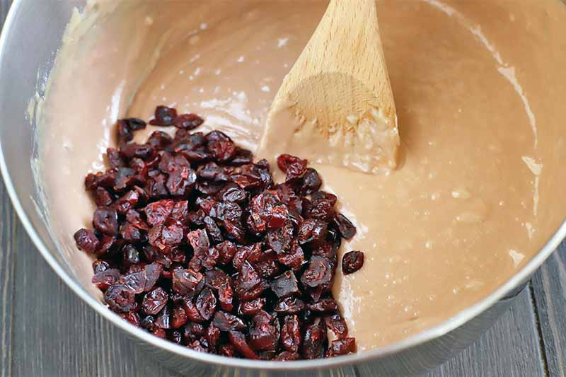 A beige quick bread batter is topped with a pile of dried cranberries, with a wooden spoon in a stainless steel mixing bowl.