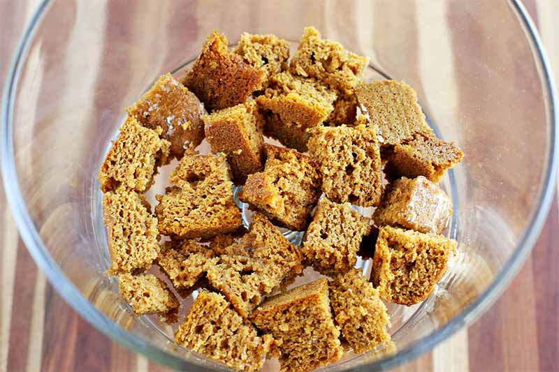 Chunks of pumpkin cake at the bottom of a round glass serving dish, on a striped wooden background.