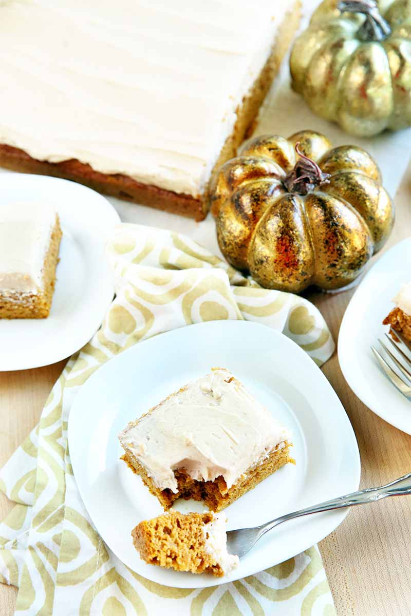 Slices of pumpkin cake with white icing are on three plates, with a forkful on the side of the plate in the foreground, and the remainder of the dessert in the background beside one gold and one orange decorative pumpkin, on a patterned gold and white cloth, on a beige surface.