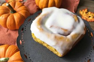 Horizontal image of one glazed breakfast bun on a dark stand in front of mini pumpkins.
