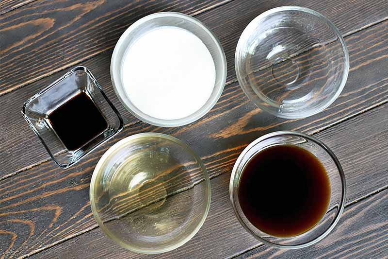 Top-down shot of one small square glass bowl of vanilla extract beside five small round glass bowls of cream, tequila, coffee, and flavored simple syrup, on a dark brown wood background.