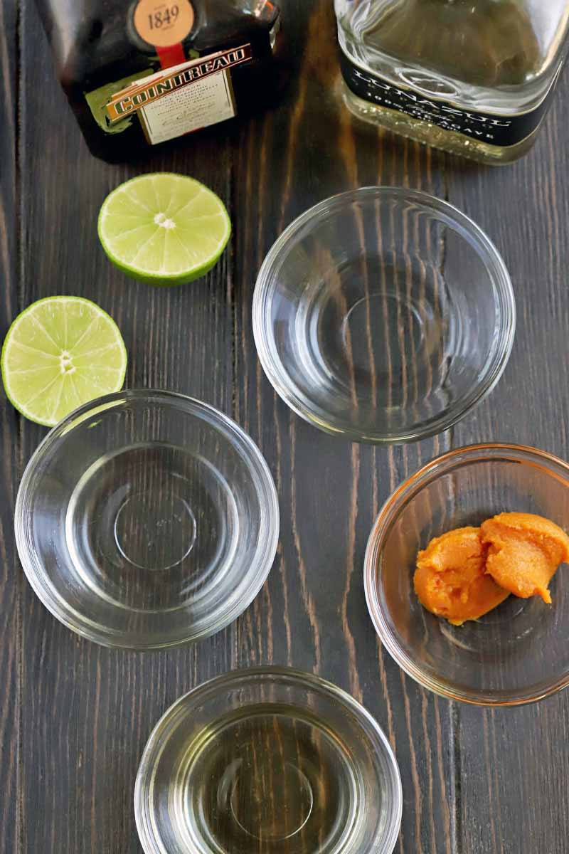 Overhead shot of four small glass bowls of spiced simple syrup, pumpkin puree, orange liqueur, and tequila, with a lime that has been cut in half, and bottles of Cointreau and tequila, on a dark brown wooden background.