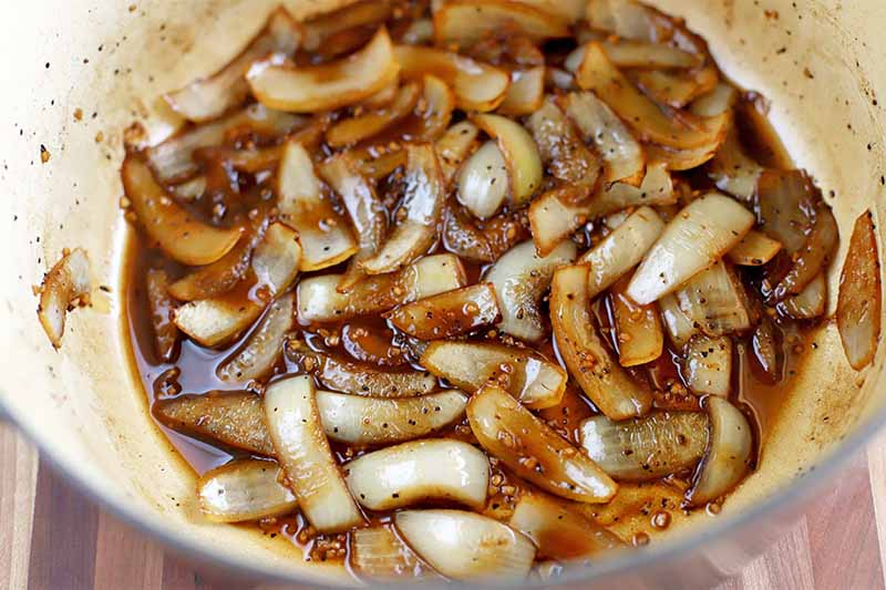 Sliced onions caramelizing in a brown liquid at the bottom of an enameled cooking pot, on a brown wood surface.