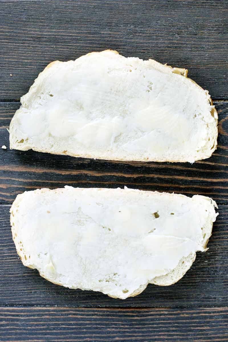 Top-down vertical shot of two slices of sourdough bread, spread with butter.
